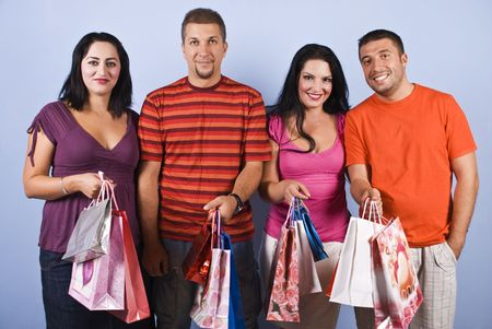 Portrait of happy four people friends  holding shopping bags looking at camera and smiling
