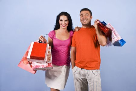 Happy young couple holding shopping bags and smiling on blue background photo