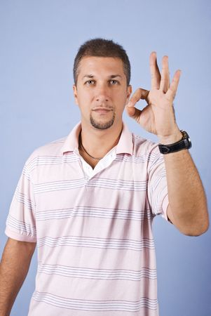 Portrait of mid adult man showing okay sign on blue background photo