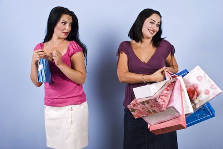 The woman in pink with little bag envy her friend wealth and success,but the rich woman it is  vain and conceited and show a superiority look photo