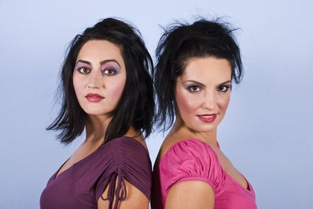 Portrait of two beauty gorgeous women standing back to back and looking at you in pink and mauve clothes and make up photo