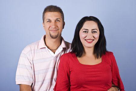 mid adult couple: Feliz pareja de adultos a mediados de pie juntos y riendo sobre fondo azul Foto de archivo