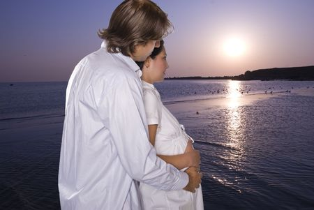 Lovely young couple expecting  a baby standing in profile,embraced and looking together at sunrise and how start a new day at sea on beach photo