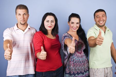 Portrait of four smiling people standing in a line and giving thumbs up on blue background photo