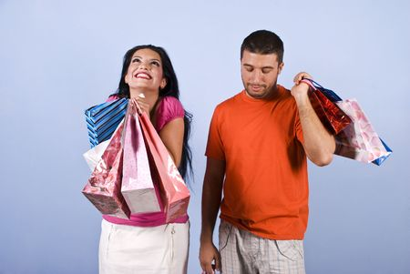 laughable: Couple at shopping  ,the young woman it is very happy and laughing with bags in her hands while the man it is sad,bored or tired of shopping