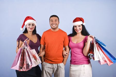 Happy three friends holding Christmas shopping bags and smiling for you on blue background photo