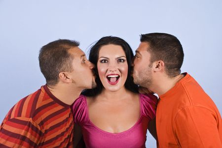 Two men trying to kiss a woman and she is surprised and making a funny face on blue background photo