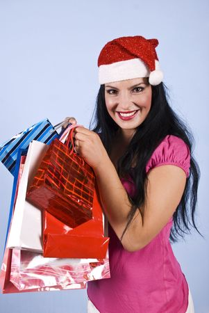 Happy brunette woman wearing a Santa hat and holding many shopping bags for Christmas  photo