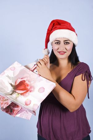 Portrait of beautiful mid adult woman smiling and holding Christmas shopping bags photo