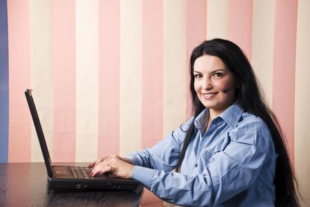 Brunette operator woman with headphones using a laptop in her office looking and smiling you ,vertical blinds background Stock Photo - 5526999
