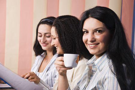 donna che beve il caff�: Tre belle donne seduti alla scrivania in ufficio, a bere un caff� donna di fronte a immagini e sorridente e le altre hanno una conversazione, ridere e discutere su alcuni documenti di giornali, tende verticali di sfondo Archivio Fotografico