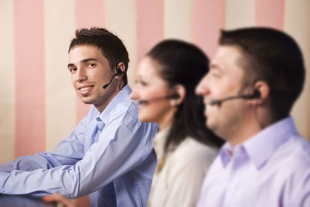 Call center operators with headset ,two men and one woman working in office,selective focus on last young man,vertical blinds background Stock Photo - 5527030
