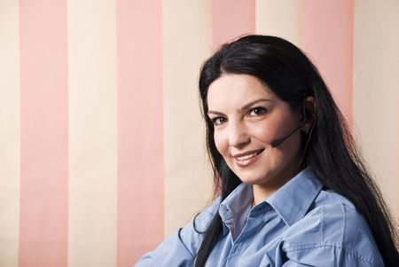 Portrait of beautiful customer service representative smiling and looking you ,vertical blinds background and copy space for text in left part of image photo