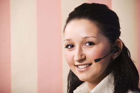 Head shot of young woman customer service smiling and looking at camera ,copy space for text message in left part of image,vertical blinds background photo