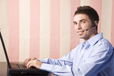 Young man customer service sitting at desktop with laptop and headphones ready to hel you,vertical blinds background photo