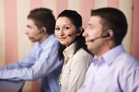 Focus on nice young woman customer service representative looking and smiling at you in the middle of two men team in office,vertical blinds background photo