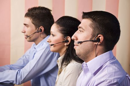 Three people customer service representative working in office , looking screen and standing in profile ,vertical blinds background Stock Photo - 5527048