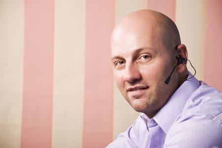 Portrait of nice customer service bald man with headset looking at you,copy space for text message in left part of image,vertical blinds background photo