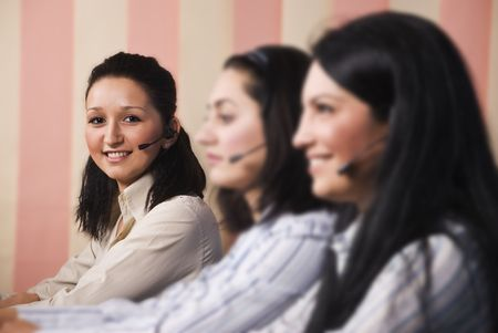 Three women customer service team  sitting in line at desktop ,focus on last young woman which looked at you and smiling photo