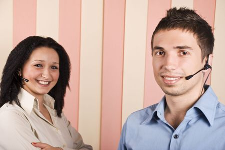 Young team with two people,woman and man customer service with headphone smiling and looking you,focus on man Stock Photo - 5527044
