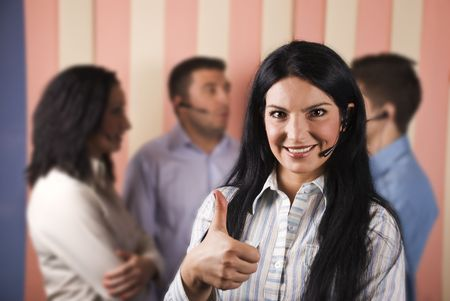 Happy customer service rep smiling and giving thumbs up in front of image with her team istanding in background and having an conversation photo