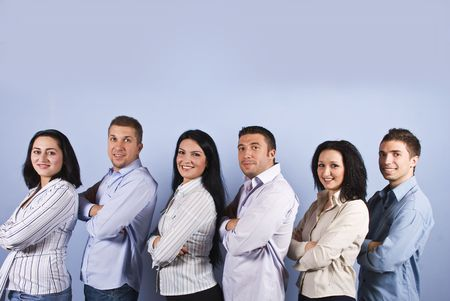 company employee: Happy business group with six smiling group standing in a line with arms folded in profile  and looking you on blue background,copy space for text message overhead