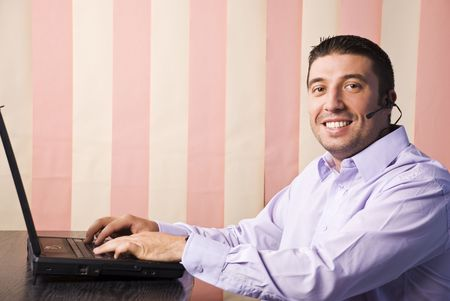 Call center man working on laptop in office and smiling at you,vertical blinds background photo