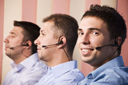 Call center operators with three men team at work in office,first man facing camera and smiling photo