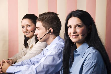 Three operators with headphones  in office sitting at desk ,two women facing you and the man standing in profile,vertical blinds background photo