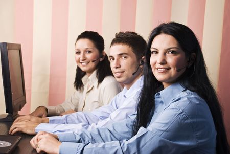 Three business people support operators working on computers in office,all workers facing camera and smiling for you,vertical blinds background photo