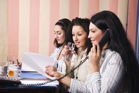 Three business women working in office, first woman speaking at phone,smiling and reading a paper with second colleague which drinking water  and being surprised and last woman looking serious while read some paperwork photo