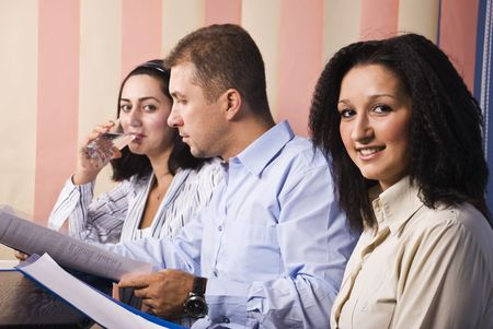 Three business people in office at work,man in middle reading some papers,last businesswoman drinking water,focus on first woman smile photo