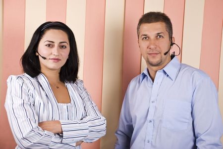 Two mid adult support operators standing with hands folded and looking you photo