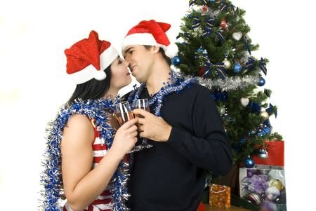 Couple kissing and celebrating with champagne the Christmas night near tree with present photo