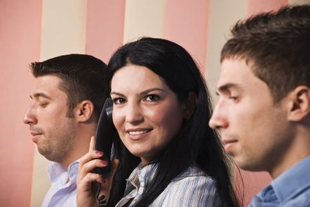 Close up of business people at work,men standing in profile and looking down reading and the woman facing camera,smiling and speak by phone photo