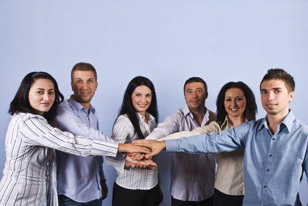 la union hace la fuerza: Grupo United grande de seis personas de negocios de pie con las manos juntas delante de fondo azul, el concepto de esp�ritu de equipo o business fuerte, espacio de la copia para los gastos indirectos de mensajes de texto