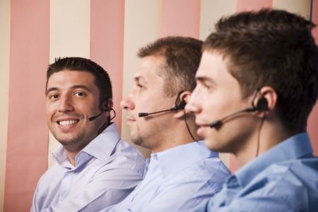 Teamwork men of customer service representative,focus on last man that looking and smiling you photo