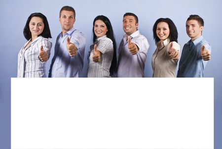 Happy group of business people with white blank banner giving thumbs up and smiling photo
