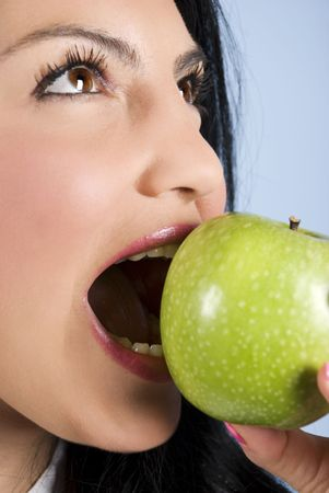 Close up of young woman  with healthy teeth looking up and taking a bite of a green apple photo