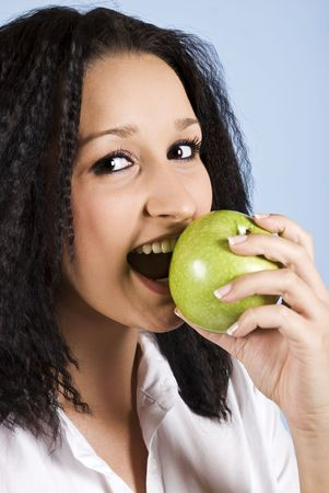 Young woman bite an green apple ,smiling and looking you on blue background Stock Photo - 5578623