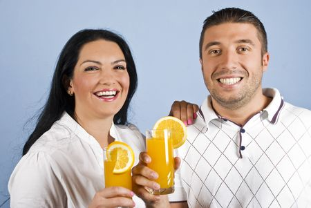 Happy laughing young couple holding glassess with orange juice,concept of healthy lifestyle on blue background photo