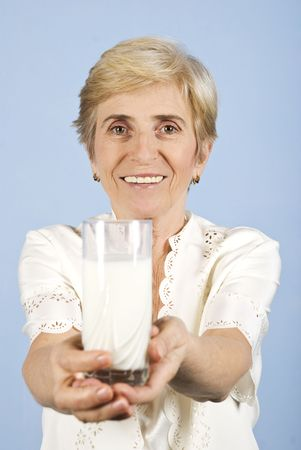 Beautiful  and healthy senior woman smiling and giving you a fresh glass of milk,blue background photo