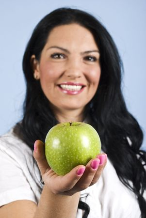 Happy woman offering and green apple,focus on apple Stock Photo - 5578628