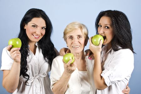 Three women friends or family,mother in the middle of two daughters smiling and holding green apples,they all wearing  white clothes on blue background photo