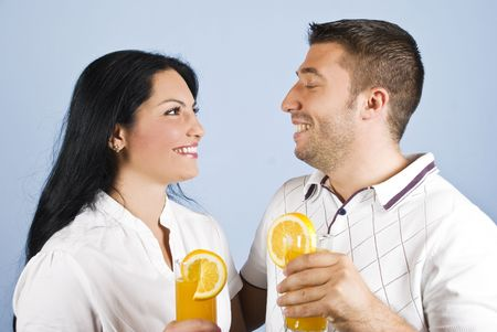 Healthy couple holding glasses with fresh orange juice,standing face to face looking at each other and laughing together photo