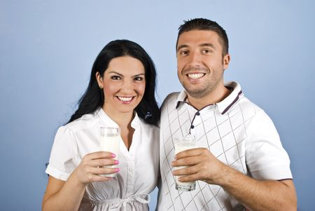 Happy couple healthy holding glasses with milk and standing together in a hug showing smiles for you on blue background photo
