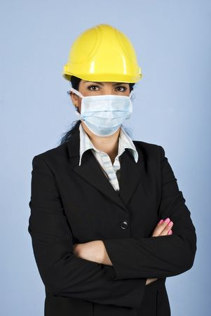 Architect woman with helmet and protective mask standing with hands folded and looking you,concept of protection from  illness at work photo