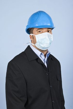 Young architect man standing in profile ,facing you and wearing helmet and protective mask,concept of protection from flu at work photo