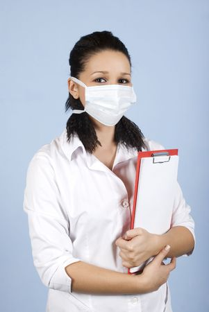 Young woman doctor wearing protective mask and holding clipboard on blue background photo