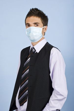 Young business man with protective mask standing on blue background,concept of protection from flu at work photo